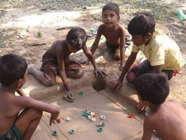Creative children make carrom board on mud, play with bottle caps